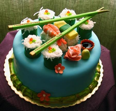 round aqua-iced cake with fondant imitation sushi and chopsticks on top
